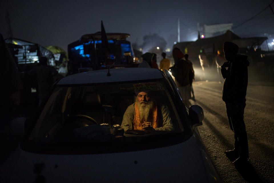 "Farmer Bhupinder Singh, 50, sits inside his car parked on a highway as a sign of protest against new farm laws, at the Delhi-Haryana state border, India, Wednesday, Dec. 2, 2020. The convoy of trucks, trailers and tractors stretches for at least three kilometers (1.8 miles). It's a siege of sorts and the mood among the protesting farmers is boisterous. Their rallying call is ""Inquilab Zindabad"" (""Long live the revolution""). (AP Photo/Altaf Qadri)"