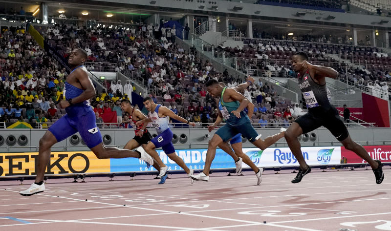 Christian Coleman, of the United States, crosses the line ahead of Aaron Brown, of Canada, and Adam Gemili, of Great Britain, in a men's 100 meter semifinal at the World Athletics Championships in Doha, Qatar, Saturday, Sept. 28, 2019. (AP Photo/David J. Phillip)