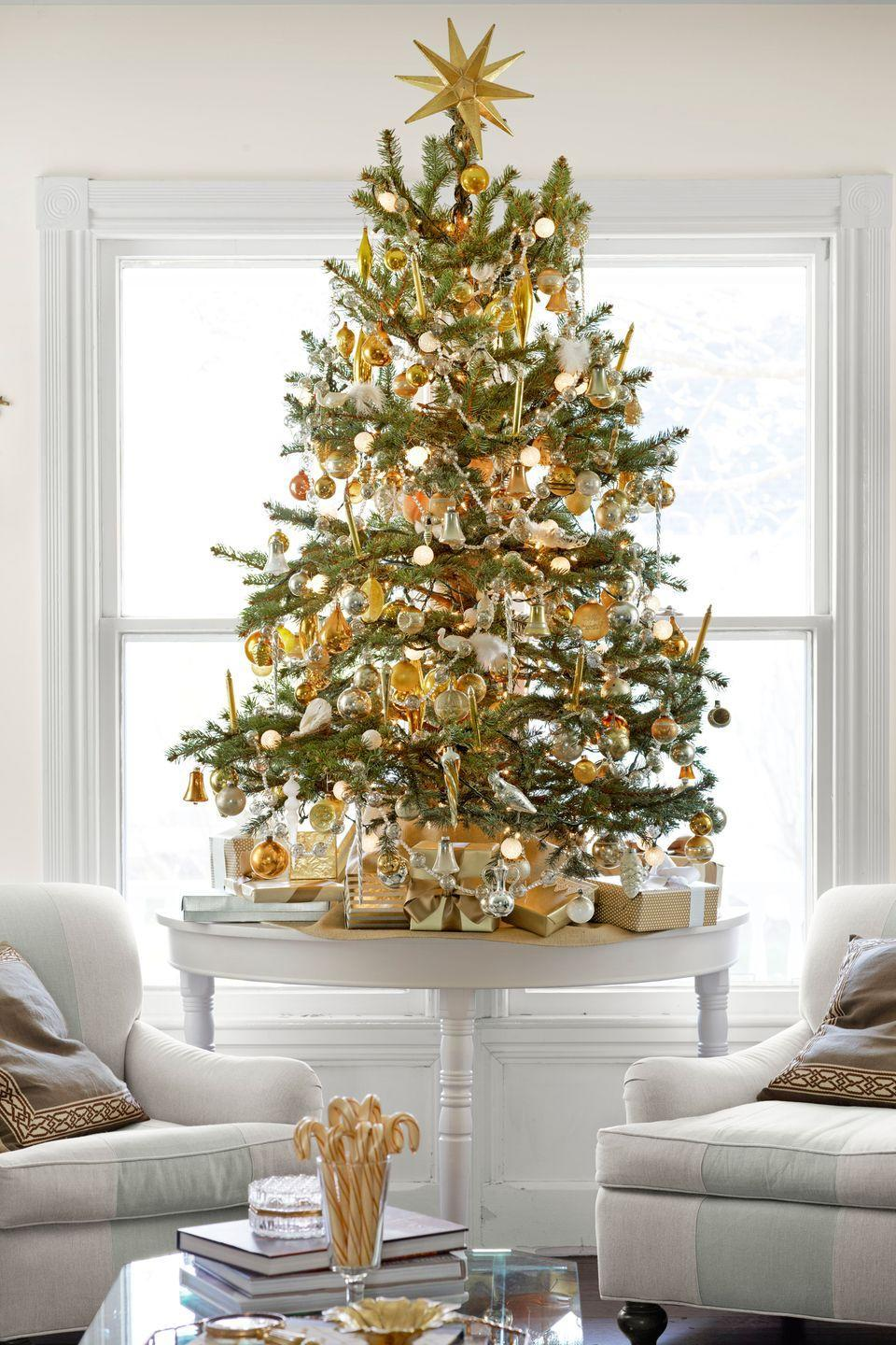 <p>Instead of one grand tree, place multiple mini-trees throughout the house. This one, on the library's demilune table, jibes with the room's palette. </p>