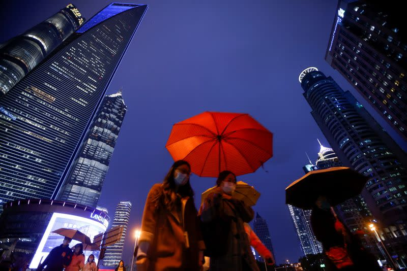 People walk with umbrellas in Lujiazui financial district in Pudong, Shanghai
