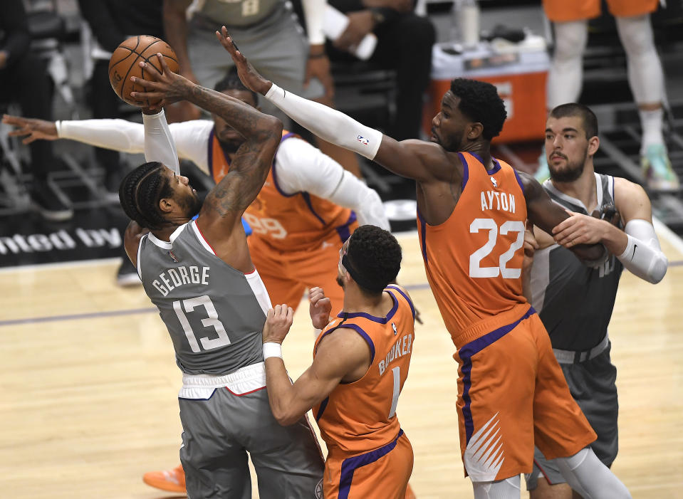LOS ANGELES, CALIFORNIA - JUNE 26: Paul George #13 of the LA Clippers shoots under pressure from Devin Booker #1 and Deandre Ayton #22 of the Phoenix Suns during the first quarter in game four of the Western Conference Finals at Staples Center on June 26, 2021 in Los Angeles, California. NOTE TO USER: User expressly acknowledges and agrees that, by downloading and or using this photograph, User is consenting to the terms and conditions of the Getty Images License  (Photo by Kevork Djansezian/Getty Images)