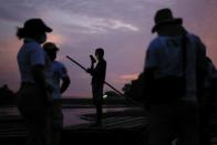 A man holds a mobile phone as immigration agents stand by the bank of the Suchiate River, while they guard the border with the National Guard to prevent a migrant caravan of Central Americans from entering, in Ciudad Hidalgo