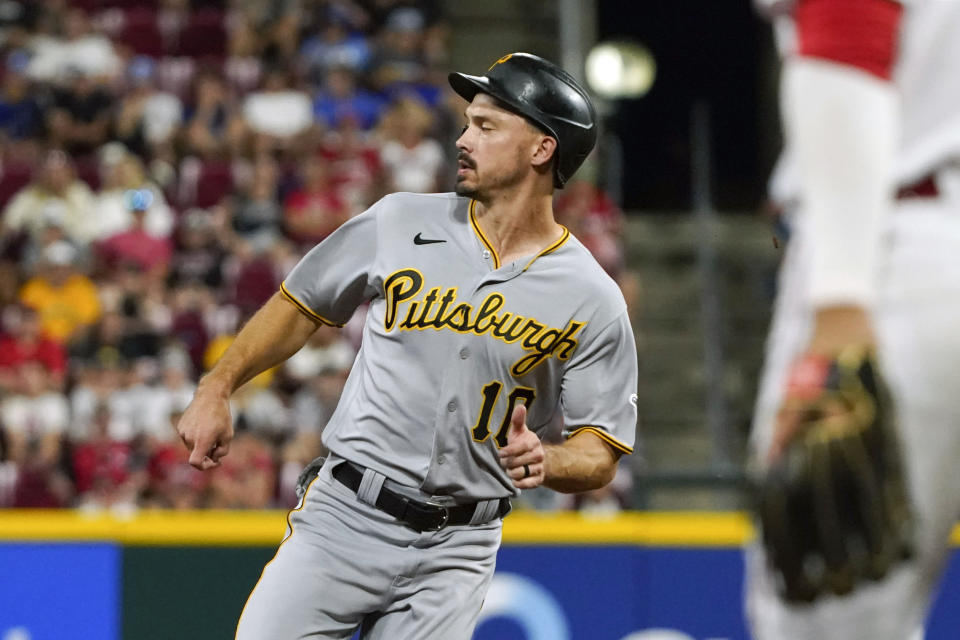 Pittsburgh Pirates' Bryan Reynolds (10) goes to third base on an RBI single hit by Ke'Bryan Hayes in the fifth inning of a baseball game against the Cincinnati Reds in Cincinnati on Thursday, Aug. 5, 2021. (AP Photo/Jeff Dean)