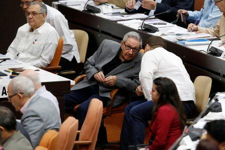 Cuba's former President Raul Castro (C-L) talks to his grandson and bodyguard Raul Rodriguez Castro during a session of the National Assembly in Havana