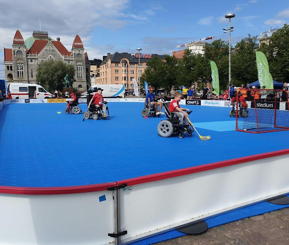 Athletes in wheelchairs playing hockey on an outdoor pitch