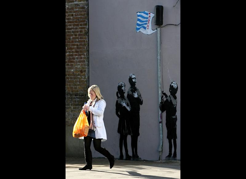 LONDON - MARCH 04: A lady with a shopping bag passes a recent Banksy work on a wall on March 5, 2008 in London, England. The grafitti shows a child raising a Tesco's plastic bag as a flag. Gordon Brown has said he will force retailers to help reduce the use of plastic bags if they do not take action voluntarily. (Photo by Cate Gillon/Getty Images)