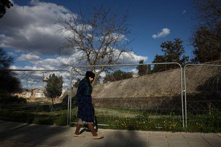 A woman walks next to a fence of the UN-controlled buffer zone in Nicosia, Cyprus February 16, 2017. REUTERS/Yiannis Kourtoglou