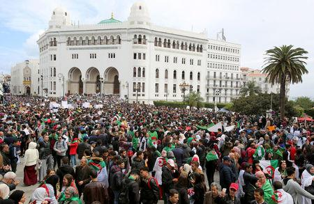 People carry national flags and banners during a protest calling on President Abdelaziz Bouteflika to quit, in Algiers