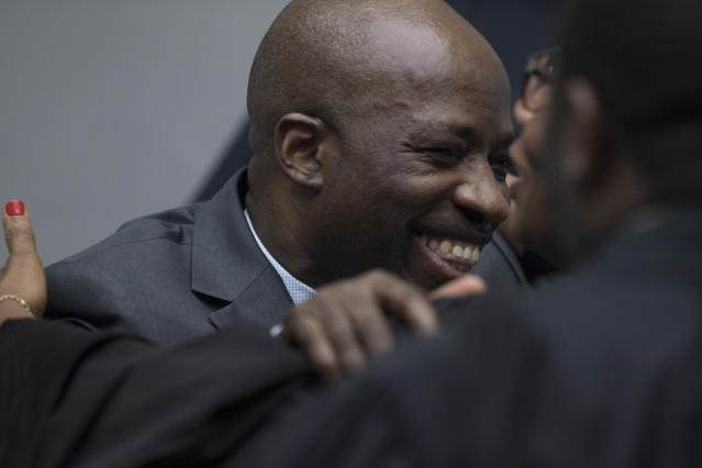Former Ivory Coast government minister Charles Ble Goude hugs his legal team at the courtroom of the International Criminal Court in The Hague, Netherlands, Tuesday, Jan. 15, 2019, where judges acquitted former president Laurent Gbagbo and Charles Ble Goude of crimes committed during the 2010 election for lack of evidence. (AP Photo/Peter Dejong, Pool)