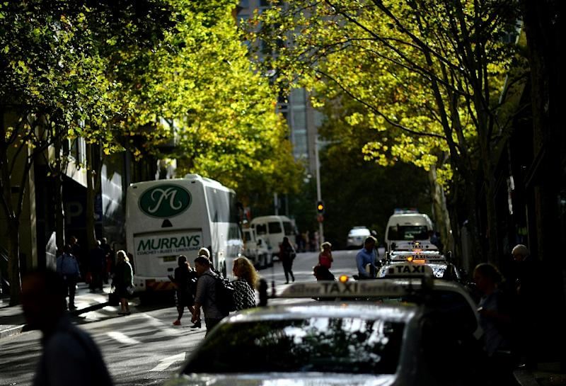 Office employees leave for home as late afternoon sunlight filters through foliage in the central business district of Sydney on March 15, 2016 (AFP Photo/Saeed Khan)