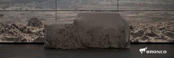 An angular SUV is shown under a cover in front of a rocky background
