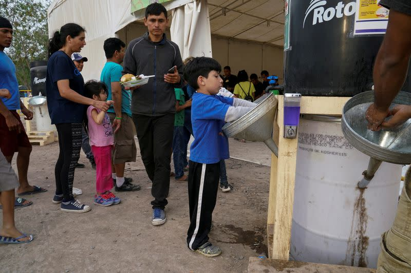 FILE PHOTO: An asylum-seeking child washes his hands at a migrant encapment in Matamoros