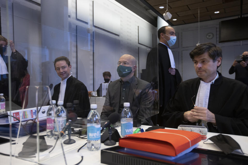 Lawyers for Shell, rear, pass Milieudefensie director Donald Pols, center, and lawyer Roger Cox, right, at the start of the court case of Milieudefensie, the Dutch arm of the Friends of the Earth environmental organization, against Shell in The Hague, Netherlands, Tuesday, Dec. 1, 2020. A landmark legal battle opened as climate change activists in the Netherlands go to court seeking an order for energy giant Shell to rein in its carbon emissions. (AP Photo/Peter Dejong, Pool)