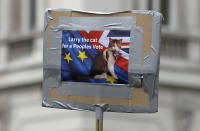 FILE - In this Saturday, March 23, 2019 file photo, demonstrators carry a poster with a picture of 10 Downing Street's cat Larry during a Peoples Vote anti-Brexit march in London. Monday, Feb. 15, 2021 marks the 10th anniversary of rescue cat Larry becoming Chief Mouser to the Cabinet Office in a bid to deal with a rat problem at 10 Downing Street. (AP Photo/Kirsty Wigglesworth, File)