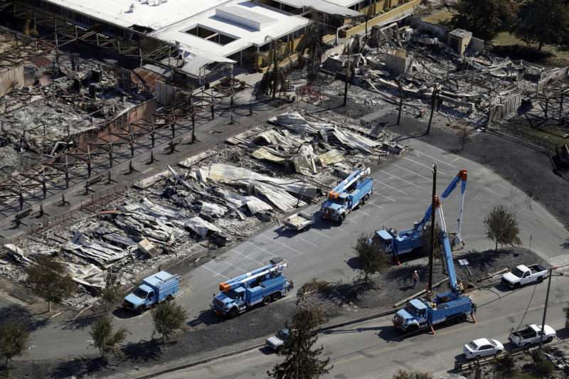 FILE - In this Oct. 14, 2017, file photo, PG&E crews work on restoring power lines in a fire ravaged neighborhood in an aerial view in the aftermath of a wildfire in Santa Rosa, Calif. PG&E says it could cut off power to a large swath of Northern California later this week to prevent its equipment from starting wildfires during hot, windy weather. The utility says power could be shut off in 30 counties in central and Northern California starting Wednesday, Oct. 9, when hot weather and strong winds are forecast, and through Thursday. (AP Photo/Marcio Jose Sanchez, File)