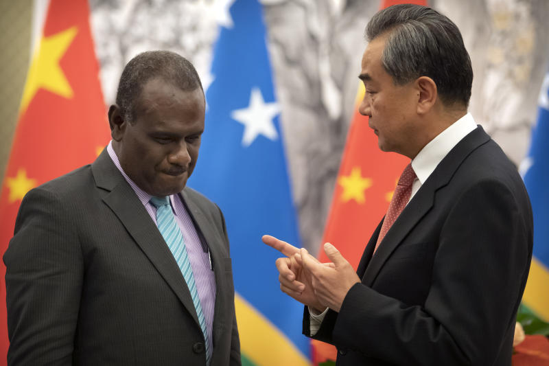 Solomon Islands Foreign Minister Jeremiah Manele, left, and Chinese Foreign Minister Wang Yi talk during a ceremony to mark the establishment of diplomatic relations between the Solomon Islands and China at the Diaoyutai State Guesthouse in Beijing, Saturday, Sept. 21, 2019. (AP Photo/Mark Schiefelbein, Pool)