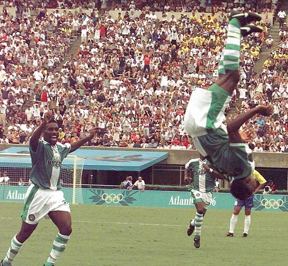 """Nigeria's Celestine Babayaro (R) makes a flip after scoring a goal against Brazil during the Olympic soccer semi-final Brazil vs Nigeria in Athens, Ga., on July 31, 1996. Nigeria won 4-3.<span class=""""copyright"""">Gabriel Bouys—AFP via Getty Images</span>"""