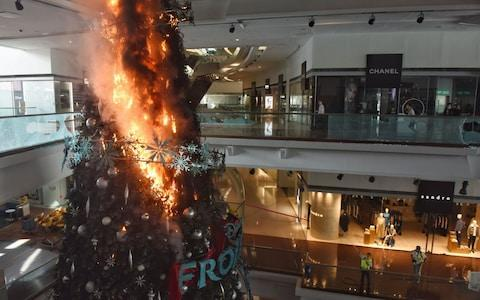 Christmas tree burns after protesters set fire to it at Festival Walk shopping mall in Kowloon Tong - Credit: MIGUEL CANDELA/EPA