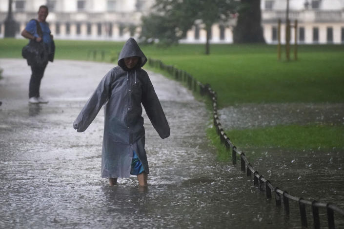 A woman walks through a flooded path in St James's Park in central London, Sunday July 25, 2021. Thunderstorms bringing lightning and torrential rain to the south are set to continue until Monday it is forecast. (Victoria Jones/PA via AP)
