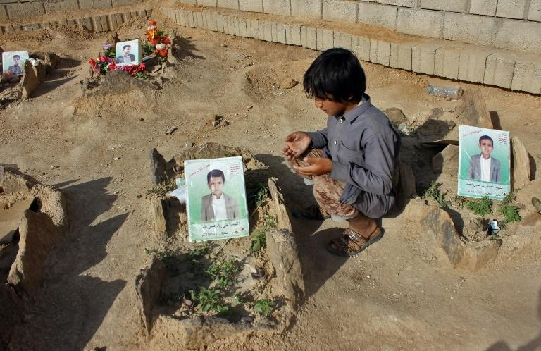 A Yemeni child recites a prayer by the graves of schoolboys who were killed when an August 9 Saudi-led coalition air strike hit their bus in a Huthi rebel stronghold, killing 51 people