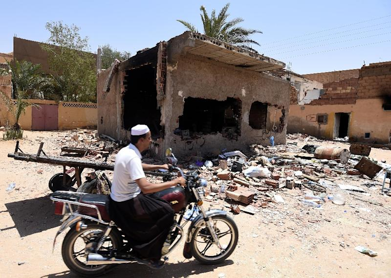 A man from the Berber community rides a motorcycle a wrecked house on July 9, 2015 following clashes between Berbers and Arabs in the Algerian town of Guerara (AFP Photo/Farouk Batiche)