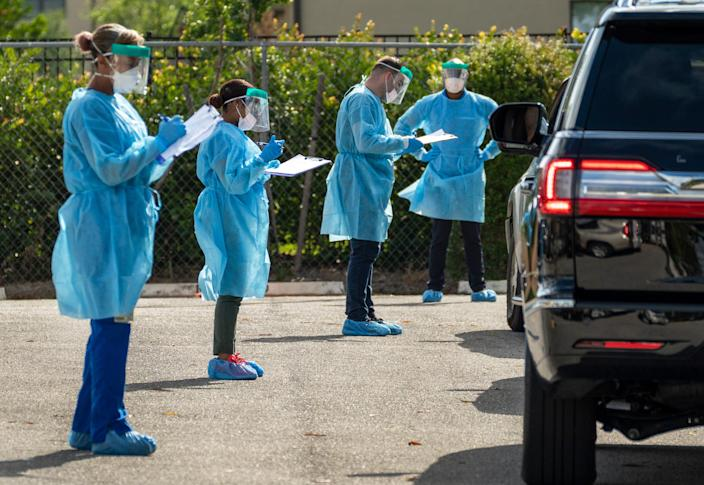 Health care workers screen patients who will be tested for COVID-19 at the FoundCare drive-thru testing station in Palm Springs, Fla., on March 19.