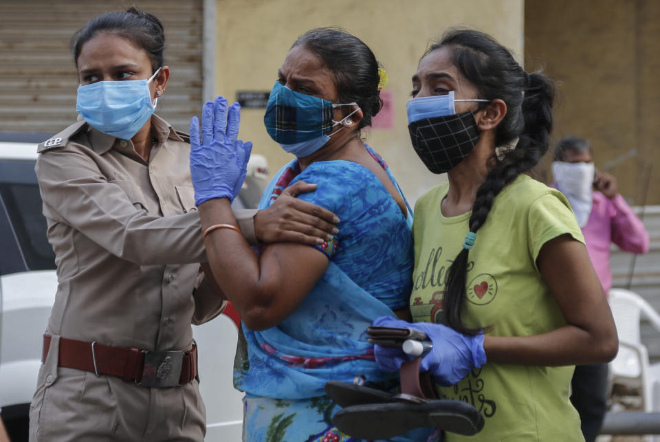 Relatives of a patient who died of COVID-19, mourn outside a government COVID-19 hospital in Ahmedabad, India, Tuesday, April 27, 2021. The COVID-19 death toll in India has topped 200,000 as the country endures its darkest chapter of the pandemic yet. (AP Photo/Ajit Solanki)
