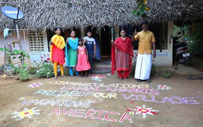 Arulmozhi Sudhakar, second right, a village councilor, gives a thumbs-up as she poses with her family and friends - Aijaz Rahi/AP