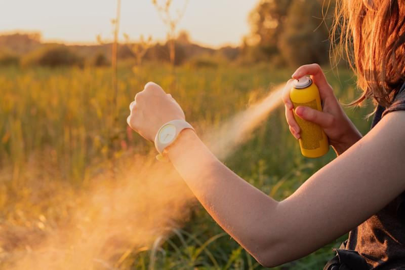 Close-up of young female backpacker tourist applying bug spray on hands (Photo: Photoboyko via Getty Images)