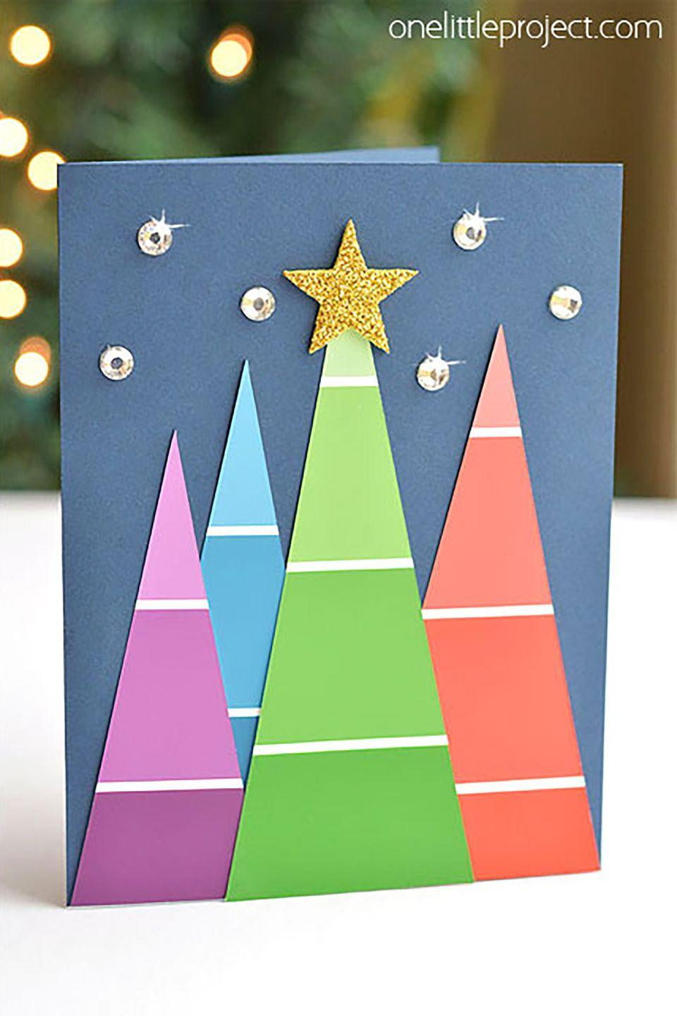"""<p>Reuse old paint chips to create a colorful forest of festive Christmas trees you can send out to loved ones.</p><p><strong>Get the tutorial at <a href=""""http://onelittleproject.com/paint-chip-christmas-cards/"""" rel=""""nofollow noopener"""" target=""""_blank"""" data-ylk=""""slk:One Little Project"""" class=""""link rapid-noclick-resp"""">One Little Project</a>.</strong><br></p><p><a class=""""link rapid-noclick-resp"""" href=""""https://www.amazon.com/Beading-Station-1440-Piece-Brilliant-Rhinestones/dp/B007G6M8GA/?tag=syn-yahoo-20&ascsubtag=%5Bartid%7C10050.g.3872%5Bsrc%7Cyahoo-us"""" rel=""""nofollow noopener"""" target=""""_blank"""" data-ylk=""""slk:SHOP RHINESTONES"""">SHOP RHINESTONES</a></p>"""