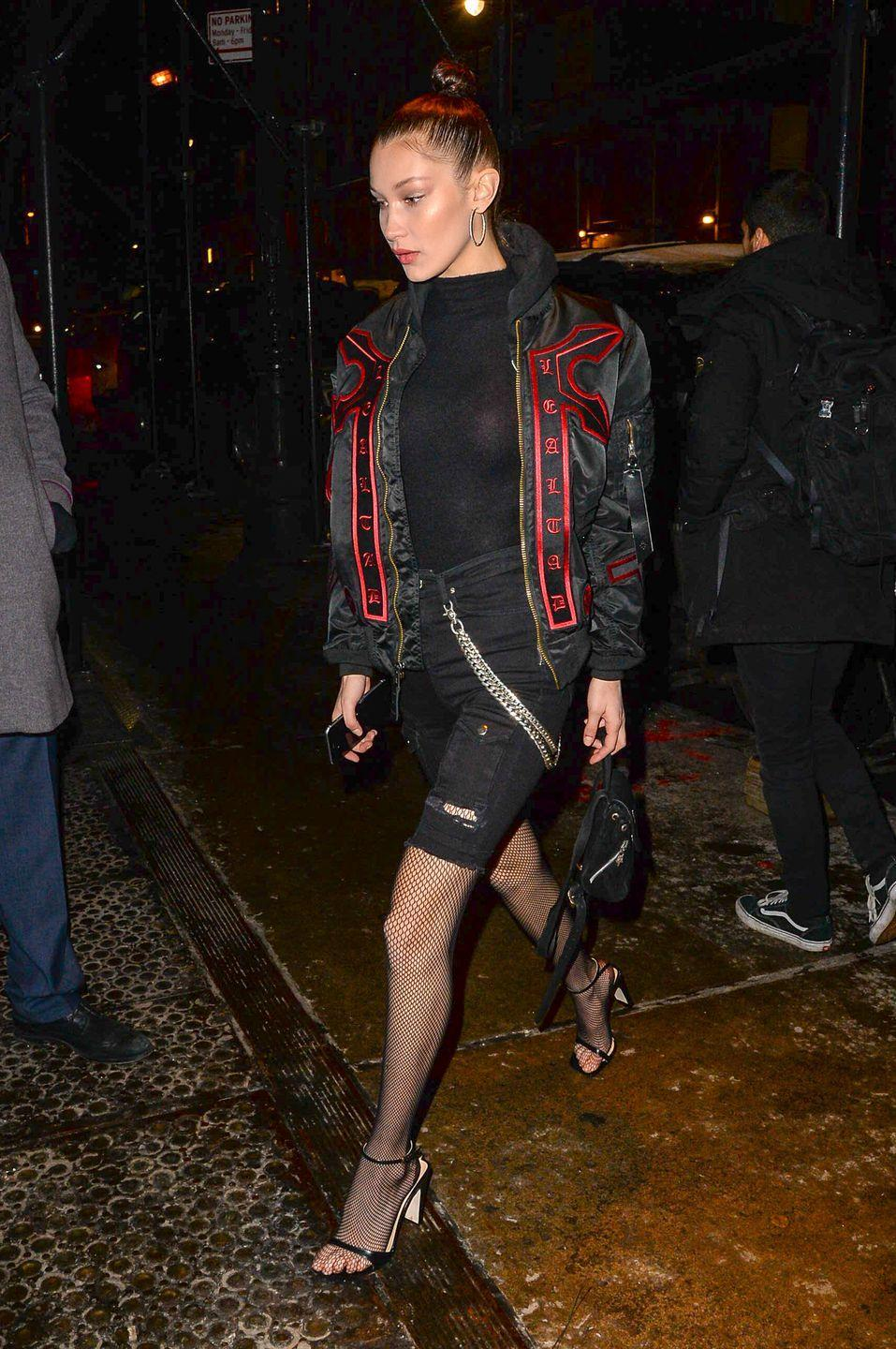 <p>Out in NYC wearing a Marcelo Burlon x Alpha Industries jacket over a black high-neck top and distressed cut-off jeans with Wolford fishnet tights and ankle-strap sandals. </p>