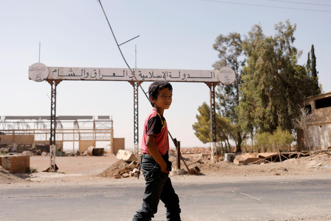 A boy walks past a sign which reads 'Islamic State in Iraq and Syria' as fighting continues between the Syrian Democratic Forces and Islamic State militants in Raqqa, Syria, August 20, 2017. REUTERS/Zohra Bensemra