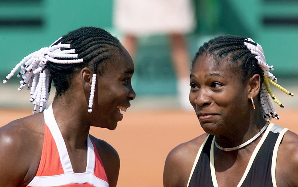 FILE - In this June 2, 1999, file photo, Venus Williams, left, and her sister Serena Williams share a light moment during their doubles tennis match against Els Callens of Belgium and Rita Grande of Italy at the French Open tennis tournament at Roland Garros stadium in Paris. (AP Photo/Laurent Rebours, File)