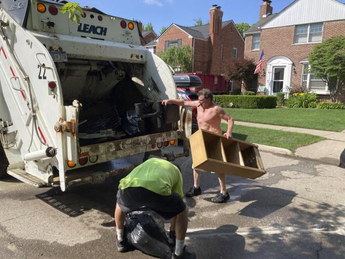 Trash is thrown out in Grosse Point Farms, Mich., Sunday, June 27, 2021. Residents in the Detroit area were cleaning up Sunday after flooding in the area overloaded sewer systems, damaged homes and knocked out power for thousands. (AP Photo/Ed White)