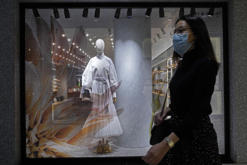 A woman wearing a face mask walks past a fashion shop in Hong Kong, Monday, March 30, 2020. The new coronavirus causes mild or moderate symptoms for most people, but for some, especially older adults and people with existing health problems, it can cause more severe illness or death. (AP Photo/Vincent Yu)