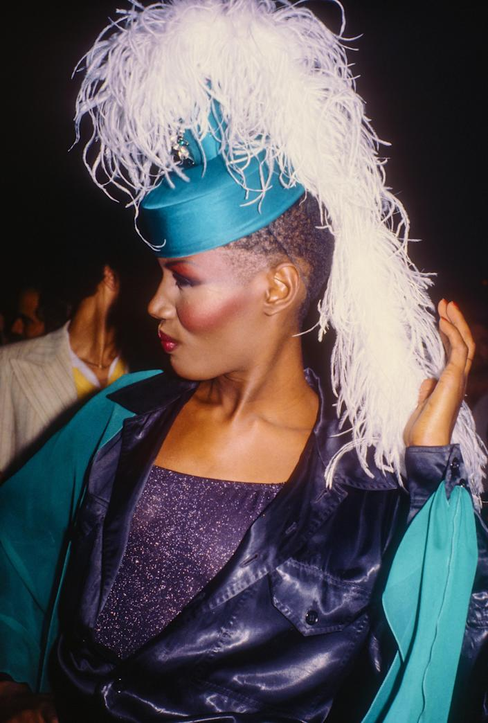 Photo of Grace Jones in bright blush and a feather adorned hat