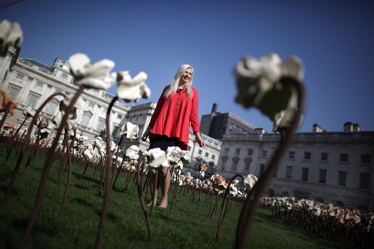 LONDON, ENGLAND - MARCH 15:  In spring sunsunshine employee Rachel Ingram walks through the 'Out of Sync' art installation on a grass meadow at Somerset House on March 15, 2012 in London, England. Chilean artist Fernando Casasempere hand crafted the 10,000 clay flowers that dominate the Edmond J. Safra Fountain Court. The installation is open to the public at Somerset House from March 16th to April 27th 2012.  (Photo by Peter Macdiarmid/Getty Images for Somerset House Trust)