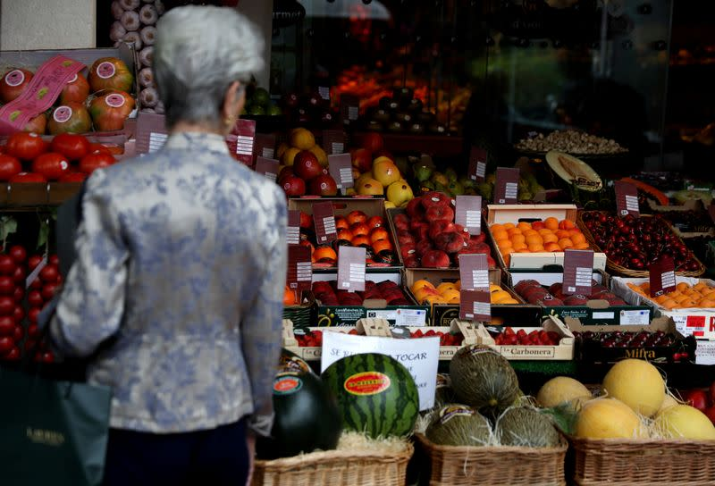 FILE PHOTO: A woman looks at fruits on display outside a greengrocery in Madrid