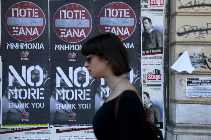 A woman walks past posters protesting a visit to Greece by German Chancellor Angela Merkel, displayed in central Athens, Friday, April 11, 2014. The left-wing main opposition party, Syriza, issued the the poster and is backing protests planned Friday. Some 5,000 police officers are on duty for Merkel's visit, that is talking place a day after Greece returned to international markets with a 5-year bond sale, following a four-year absence. (AP Photo/Dimitris Messinis)