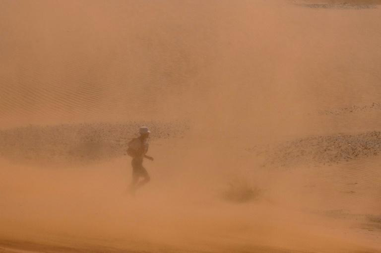 Sand blasted: A runner battles the elements on the third stage. (AFP/JEAN-PHILIPPE KSIAZEK)