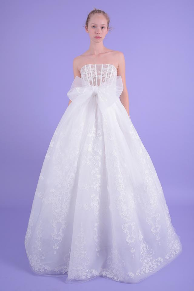 <p>This strapless dress with lace is sure to be a wedding hit. The full A-line skirt, corset-like bodice, and large bow at the waist provide an regal feel to this gown.</p>