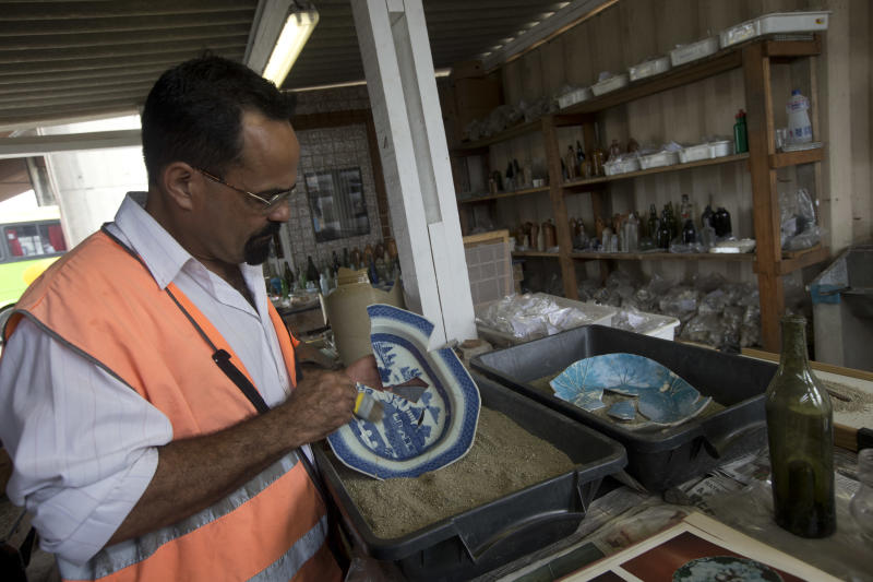 """Archeologist and team leader Claudio Prado de Mello cleans a partially recovered porcelain plate in a subway expansion area in Rio de Janeiro, Brazil, Wednesday, Sept. 18, 2013. The area, which is now being used as a construction site for Rio's massive subway expansion projects, has not only yielded an impressive number of objects but also pieces in remarkably good condition dating from the 17th through the 19th centuries. """"What is the most impressive is the intact state in which the objects are coming out of the ground in,"""" said Mello. """"In archeology we usually find very fragmented pieces, but this time we're finding whole objects."""" (AP Photo/Silvia Izquierdo)"""