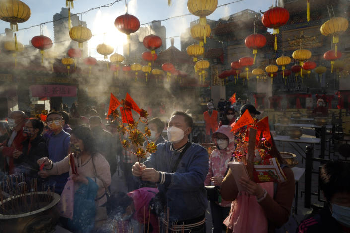 Worshippers wearing face masks to protect against the spread of the coronavirus burn joss sticks as they pray at the Wong Tai Sin Temple, in Hong Kong, Friday, Feb. 12, 2021, to celebrate the Lunar New Year which marks the Year of the Ox in the Chinese zodiac. (AP Photo/Kin Cheung)