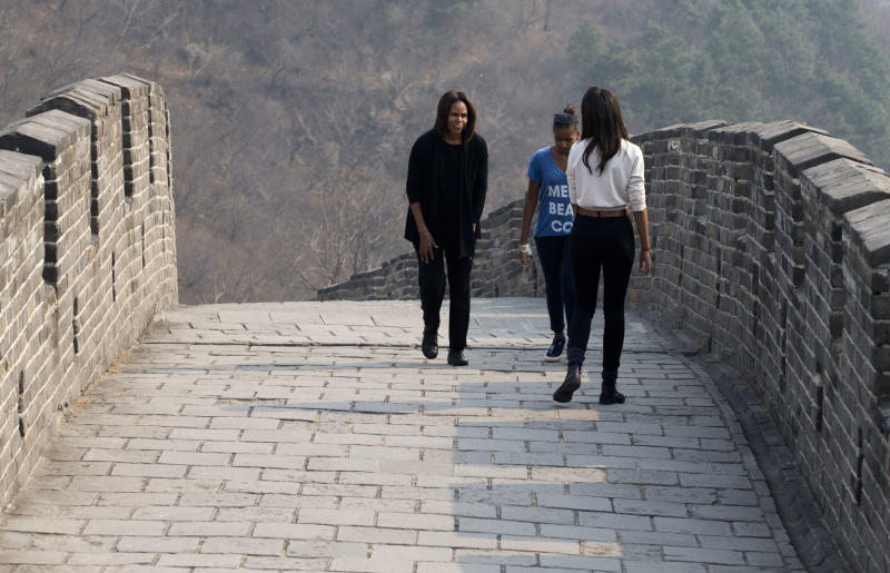 U.S. first lady Michelle Obama, left, walks with her daughters Malia, front, and Sasha as they visit the Mutianyu section of the Great Wall of China in Beijing Sunday, March 23, 2014. (AP Photo/Andy Wong)