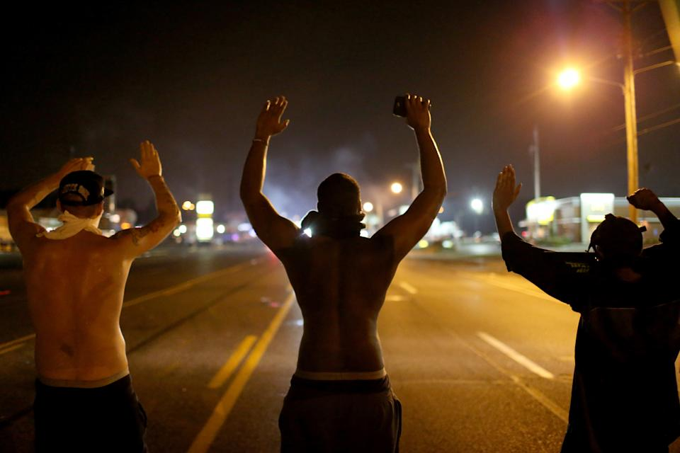 Protesters raise their hands in the middle of a roadway on August 17, 2014 in Ferguson, Missouri. (Getty Images)