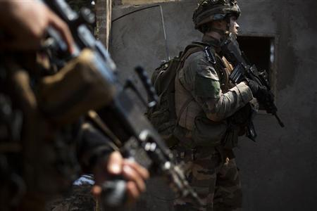 French peacekeeping soldiers search a looted house in the district of Combattant near the airport of the capital Bangui