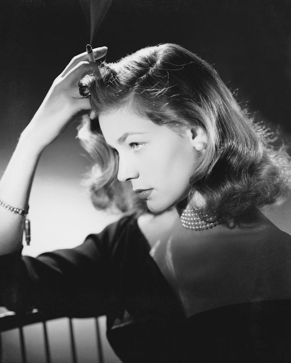 <p>Lauren Bacall's smoking habit was often incorporated into her movie roles—of course, this was before people knew of the related dangers. Off-screen the actress's cigarette was never far from her hand and even used as an accessory, as seen here. </p>