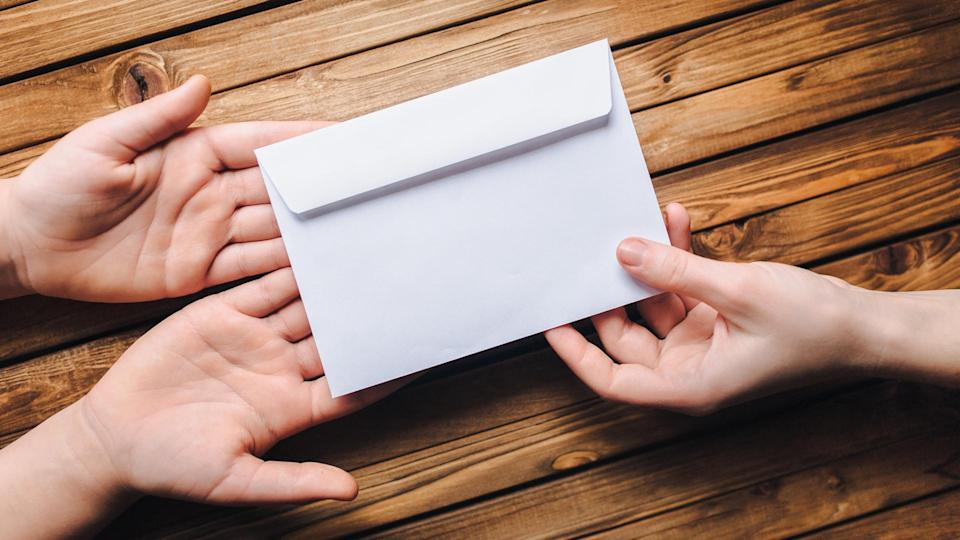 handing over an envelope of donations