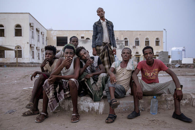 "In this July 21, 2019 photo, Ethiopian migrants sit together and smoke, as they take shelter in the ""22nd May Soccer Stadium,"" destroyed by war, in Aden, Yemen. Over the summer, the stadium became a temporary refuge for thousands of migrants. At first, security forces used it to house migrants they captured in raids. Other migrants showed up voluntarily, hoping for shelter. The IOM distributed food at the stadium and arranged voluntary repatriation back home for some. The soccer pitch and stands became a field of tents, with clothes lines strung up around them. (AP Photo/Nariman El-Mofty)"
