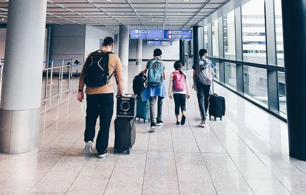 The Nelson family navigate one of many airport stops on their two-week commute home from Saudi Arabia under Australia's strict arrivals cap.